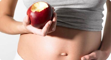 Femme enceinte présentant une pomme croquée.