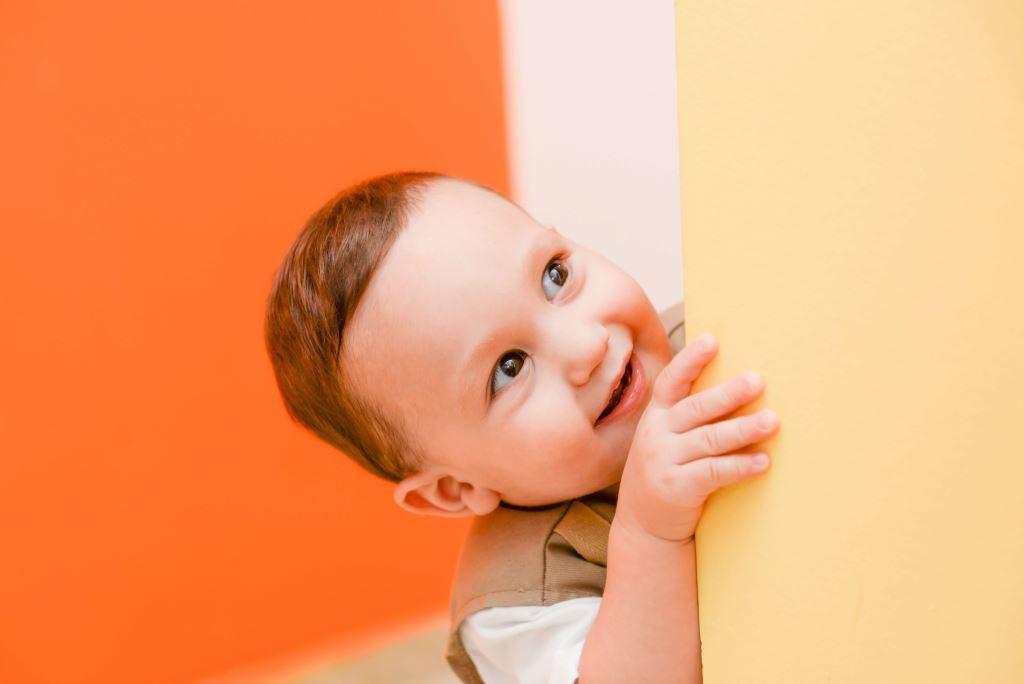 Petit garçon souriant passant la tête au détour d'un mur.
